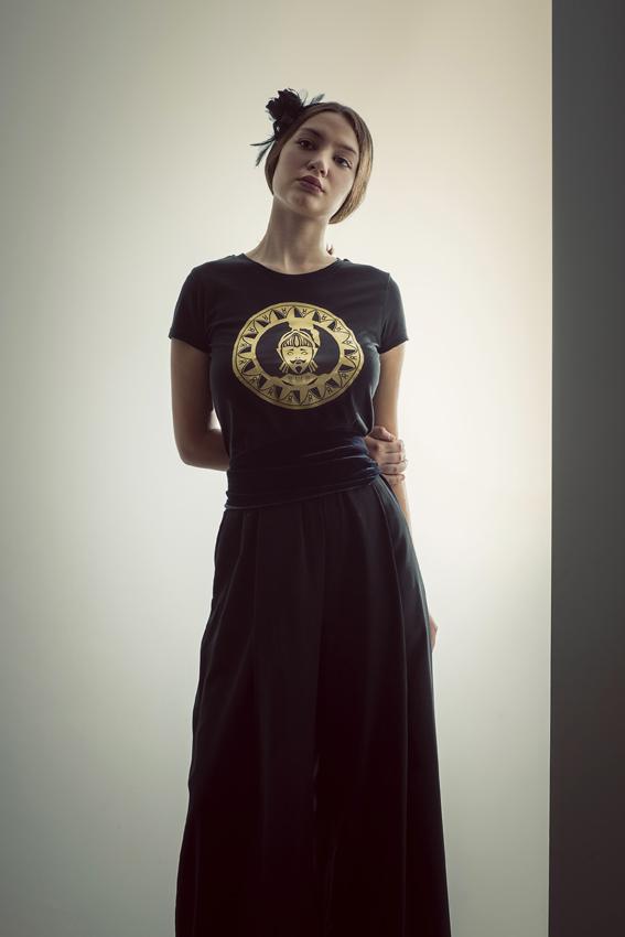 modella con t-shirt nimabi nera, disegno oliviero oro